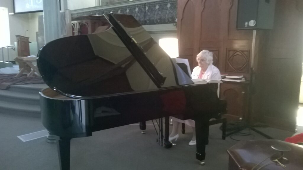 Miss Dorothy McNeill playing the baby Grand Piano